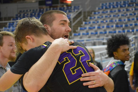 Alexandria Senior High coach Lance Brasher (left) hugs sophomore Noah Jonker after the Trojans' 38-37 victory over Bonnabel in the Class 5A championship game Friday.