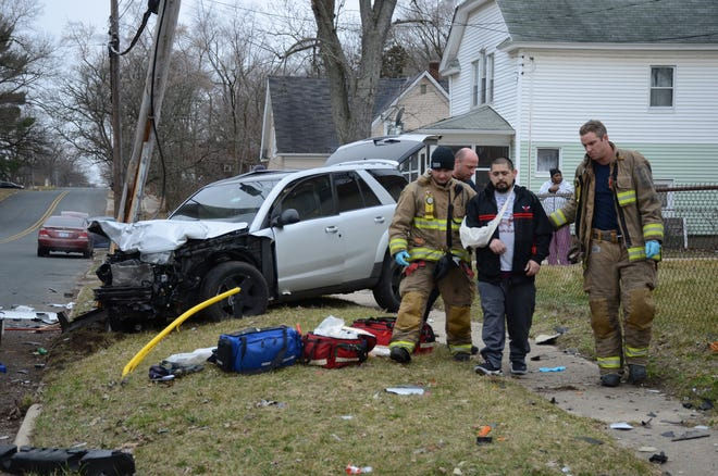 One of five people injured in a Saturday crash is helped to an ambulance.