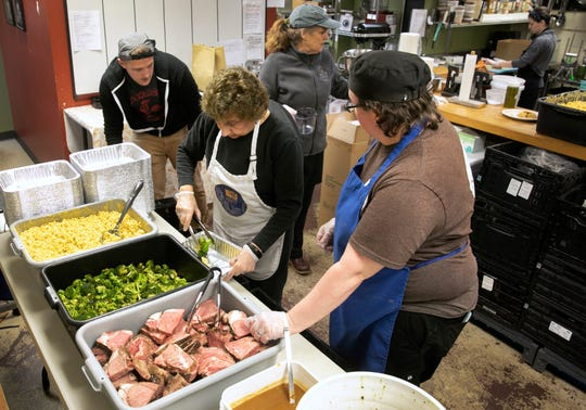 Suzy DeYoung, executive director and founder, with hat, and her team at La Soupe have been rescuing food and feeding those in need since 2014. With Cincinnati Public Schools closed due to the coronavirus, DeYoung jumped into action to create family meals for families. The team was preparing meals Saturday, March 14, 2020 that include mac and cheese, broccoli and prime rib and au jus, along with a chimichurri sauce. They are also offering turkey and chicken as a protein. (L-R) Wes Fowler, new volunteer, Jeanette Rost, one of the original volunteers and head chef Miranda Maszk.