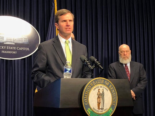 Kentucky Gov. Andy Beshear discusses developments in Kentucky regarding the new coronavirus on Friday in Frankfort, Kentucky. Acting state health and family services Secretary Eric Friedlander looks on as the governor speaks to reporters at the Kentucky Capitol.