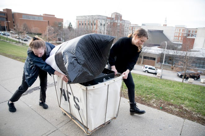 Kailey Akins, a UC sophomore, left, and Olivia Schmitt, UC freshman, move out of Calhoun Residents Hall at the University of Cincinnati in Clifton on Friday, March 13, 2020. Miami University and the University of Cincinnati announced Friday that they will shift to remote learning for the remainder of the semester.