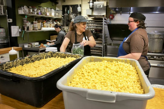 Suzy DeYoung, executive director and founder of La Soupe, center, works with head chef Miranda Maszk to prepare family meals for Cincinnati Public School families, Saturday, March 14, 2020. La Soupe has been rescuing food and feeding those in need since 2014. With CPS closed due to the coronavirus, DeYoung jumped into action to create the meals that include mac and cheese, broccoli and prime rib and au jus, along with a chimichurri sauce. They are also offering turkey and chicken as a protein.