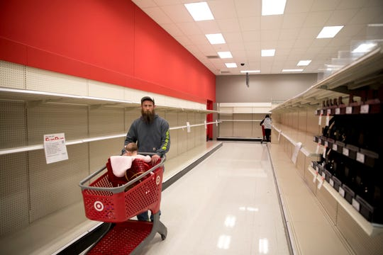 Nick Wolsing, of Alexandria, Ohio moves through the empty toilet paper and flushable wipe section at Target in Newport on March 14, 2020.