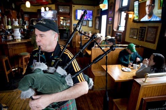 """Tommy Thompson plays the bagpipes at Molly Malone's Irish Pub & Restaurant in Covington, Ky., on Saturday, March 14, 2020. """"The Grinch didn't steal Christmas and we can't let coronavirus steal St. Patrick's Day,"""" Thompson said."""