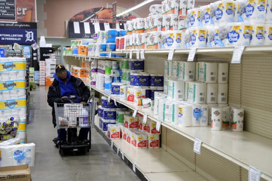 Due to the coronavirus pandemic local shoppers like Richard Smith are stocking up on water and toilet paper at Ferndale Foods in Ferndale, Michigan, Saturday, March 14, 2020.
