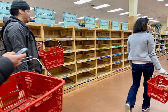 Shoppers walk past empty shelves at a Trader Joe's in Ann Arbor on Friday, March 13, 2020. Shoppers across Michigan are stocking their pantries with essentials like bread, meat, eggs, and canned goods in anticipation of a coronavirus outbreak in the area.