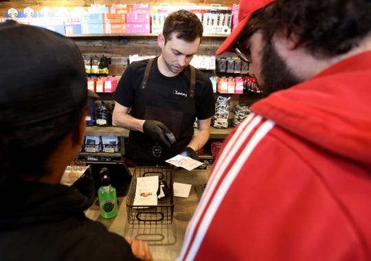 Greenhouse employee Jeremy Alain, 27, of Walled Lake rings up the order that Gustavo Amezola, 23 and girlfriend Gabrielle Butler, 23 both of Wixom placed on the opening day for recreational users at  Greenhouse, one of the first Oakland County marijuana dispensary that opened up on Saturday morning, March 14, 2020.