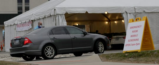 Cars drove up to a tent set up outside the McLaren hospital emergency in Macomb to be tested for the COVID-19 Saturday, March 14, 2020.