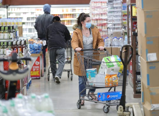 Due to the coronavirus pandemic, local shoppers, including those wearing masks, stocked up on water and toilet paper at Ferndale Foods in Ferndale, Michigan.