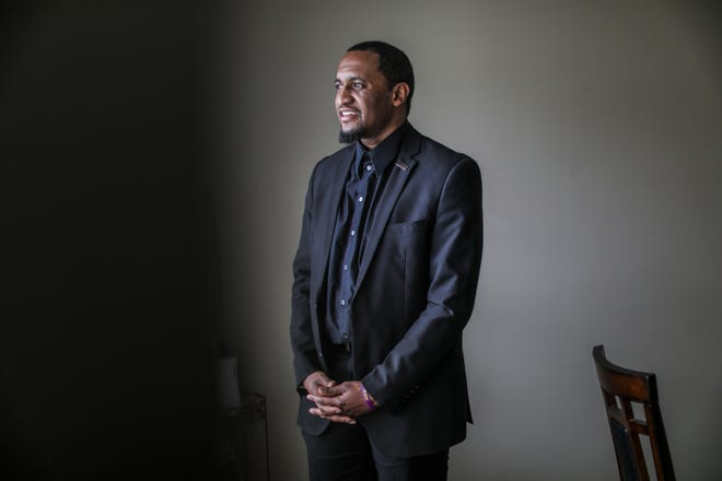 Hodari Brown, 35, of Redford suffers from PTSD, anxiety and depression as a military veteran who served in 2011-2012 and is photographed at his home on March 14, 2020. The coronavirus outbreak has at times exacerbated the symptoms of his mental illness, but he tries to stay positive in light of so much uncertainty by staying active in his faith by still attending service at Triumph Church DWO campus where he is a minister and leading a peer support group through the National Alliance on Mental Illness Metro.