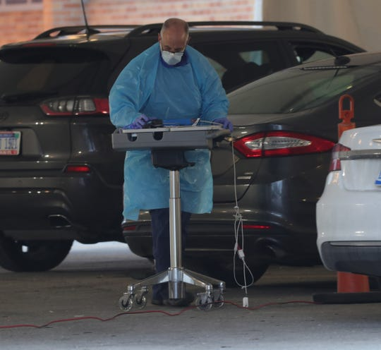 Cars drove up to a tent set up outside the McLaren hospital emergency in Macomb where RN Mike M. tested them for the COVID-19 Saturday, March 14, 2020.