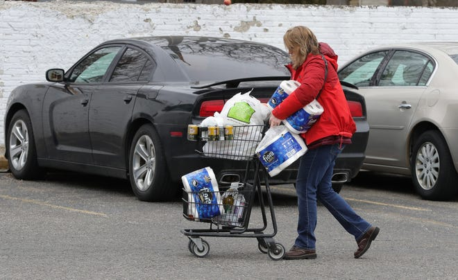 Due to the Coronavirus Pandemic local shoppers like Lori Morris are stocking up on water and toilet paper at Ferndale Foods in Ferndale, Michigan Saturday, March 14, 2020.