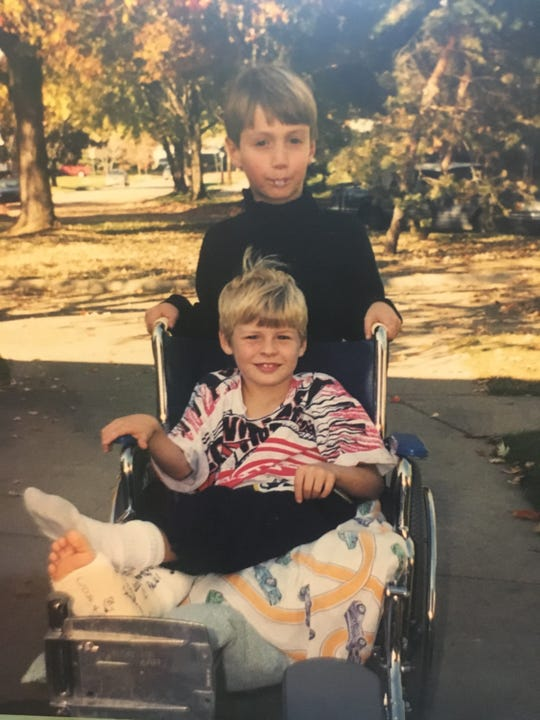 A young James Hawkins, bottom, gets a hand from neighbor Alex after breaking his leg for the first time in 1998.