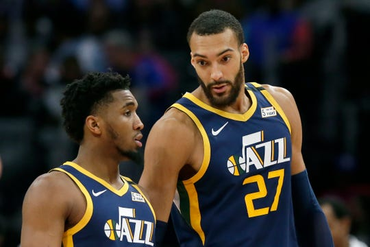 Utah Jazz center Rudy Gobert (27) talks with guard Donovan Mitchell, left, during a game against the Detroit Pistons, in Detroit. Both players have tested positive for the coronavirus.  Gobert's test result forced the NBA to suspend the season.
