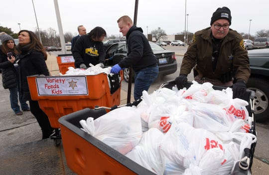 Oakland County Sheriff's deputies Mark Barton, left, and  David Barrett move crates of food into place during the giveaway.