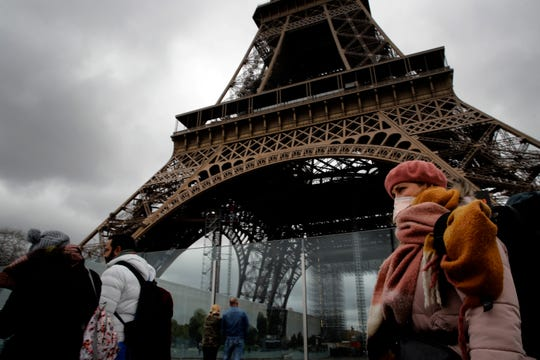 A woman wearing a mask walks pasts the Eiffel Tower closed after the French government banned all gatherings of over 100 people to limit the spread of the virus COVID-19, in Paris, Saturday, March 14, 2020.)