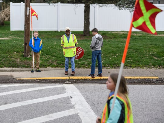 Crossing Guard Janice Outlaw, center, and members of Evansville's Dexter Elementary safety patrol wait for the bell to ring and students to start crossing the street in front of the school, Friday afternoon, March 13, 2020. After Friday, the Evansville Vanderburgh School Corporation closed all schools until March 30 in reaction to the global outbreak of COVID-19.