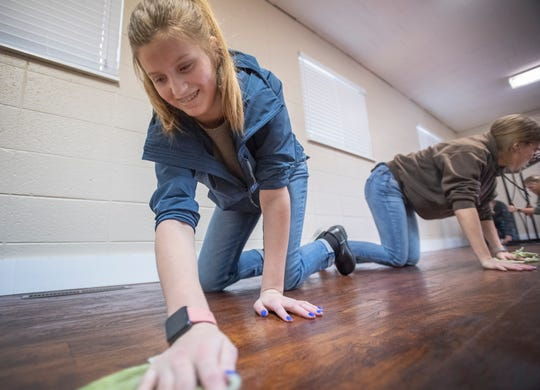 Elsje Vander Dussen wipes down a wooden floor in Providence Bible Church in Fort Collins on March 14.