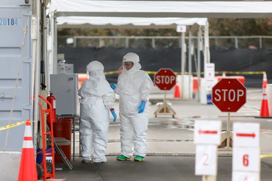 Medical University of South Carolina healthcare providers dress in protective suiting as they get ready to see patients by the hospital's drive-through tent for patients who are being tested for the COVID-19 coronavirus at the Citadel Mall parking lot Friday, March 13, 2020, in Charleston, S.C.