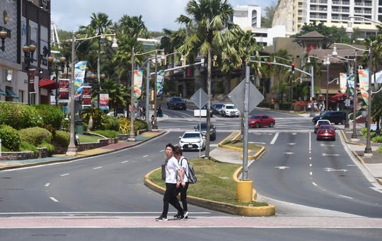 Tourists walk the streets of Tumon in the midst of the COVID-19 pandemic on March 13, 2020.