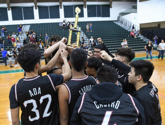 The Father Duenas Friars raise their Guam Basketball Confederation Guam National High School Championship trophy after defeating the Guam High Panthers at the University of Guam Calvo Field House in Mangilao, March 14, 2020. The Friars beat the Guam High Panthers 69-44 for the title.