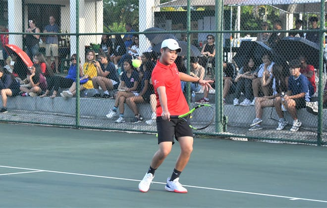 St. John's Marshall Zhang cuts the ball against No. 1 seed Mark Fontanilla of John F. Kennedy High March 13 at the Ninete Tennis Center in Hagåtña. Zhang, seeded No. 2, upset Fontanilla in an 8-6 thriller to claim the boys singles title in the high school Islandwide Tennis Tournament.