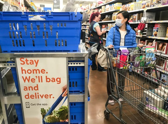 A shopper wears a medical mask while shopping for groceries at a Walmart in Clarksville, Kentucky. Shopping for large families often draws glares by other shoppers who think they are hoarding supplies.
