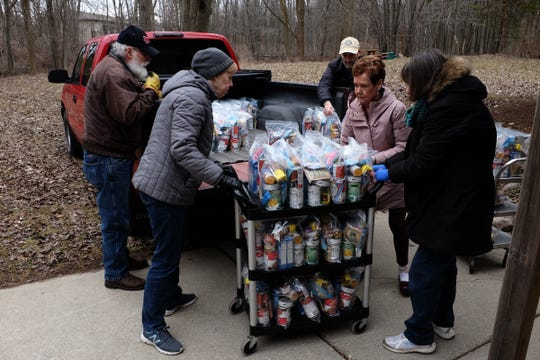 Volunteers from Delta Presbyterian Church and the Delta-Waverly Rotary Club unload packages of food for distribution to needy children as part of the Rotary Club's backpack program Saturday, March 14, 2020.  The club is using the church to store and distribute the food because the Waverly schools are closed for three-weeks due to the COVID-19 virus by Michigan's Governor Gretchen Whitmer.