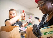 Traci Sanchez and Annie Freeman pack up food bags for families at Impact Baptist Church in Memphis,Tenn., on Saturday, March 14, 2020.