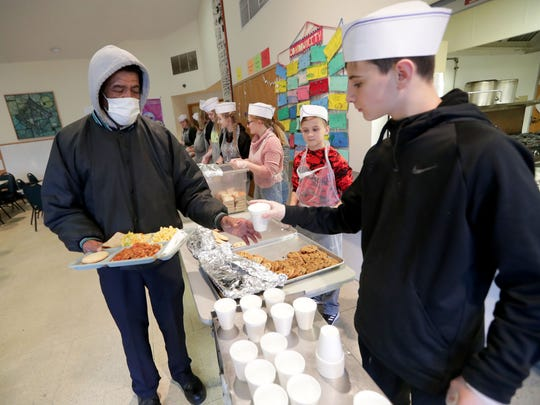 Lee Lee of Milwaukee gets a cup of milk from volunteer Ryker Morgan, 14, at The Gathering meal service held at Our Next Generation building at West Lisbon Avenue and North 35th Street in Milwaukee on Saturday. Lee said he wasn't sick and was wearing a mask as a precaution.