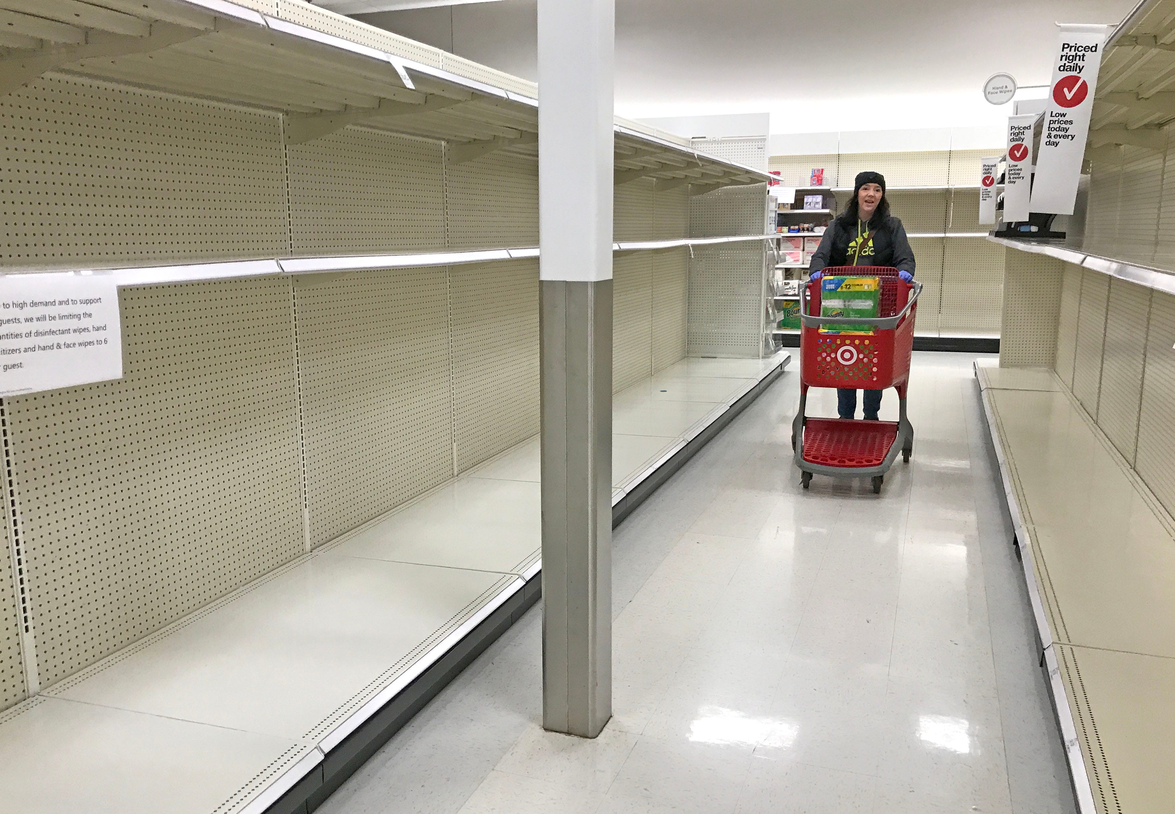 A customer walks down an empty aisle where toilet paper normally fills the shelves at Target in Menomonee Falls on March 14, 2020.