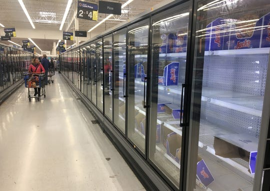 Shoppers pass by nearly empty freezers that were once filled with frozen pizzas Saturday at Walmart in Fond du Lac. According to an employee, the store ran out paper products like toilet paper, paper towels and napkins 30 minutes after stocking shelves Saturday morning. Other items that have been coveted by shoppers include frozen pizzas, frozen breaded chicken products, ice cream, eggs and cleaning supplies including detergent.