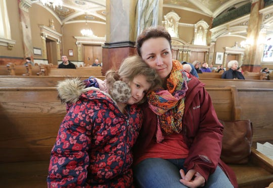 Elizabeth Kopec sits with her daughter, Maria, 7, during Mass at the Basilica of Saint Josaphat on South 6th Street in Milwaukee on Saturday.  They traveled from Mount Prospect, Illinois, because their church services were canceled in the wake of the coronavirus.