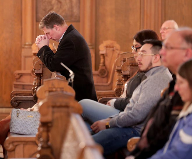 A parishioner prays during Mass at Basilica of Saint Josaphat on South 6th Street in Milwaukee on Saturday.