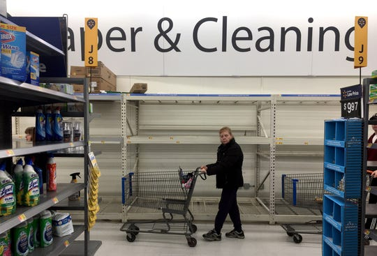 A shopper walks past shelving that was filled with paper products Saturday at Walmart in Fond du Lac.