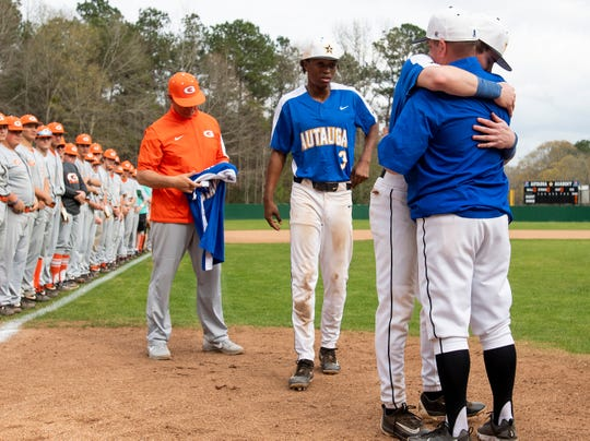 Autauga Academy coach Scott Tubbs is hugged by his son  Tyson Tubbs after presenting Glenwood coach Tim Fanning  a blue jersey before their game on the Autauga Academy campus in Prattville, Ala., on Friday March 13, 2020.
