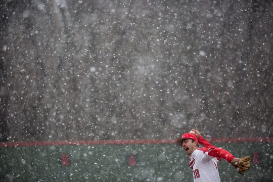 Denison University senior Max Dehon pitches through the snow Saturday in the first inning of a game against Muskingum University. The Big Red hosted the Muskies for the last game before the season was postponed due to COVID- 19.
