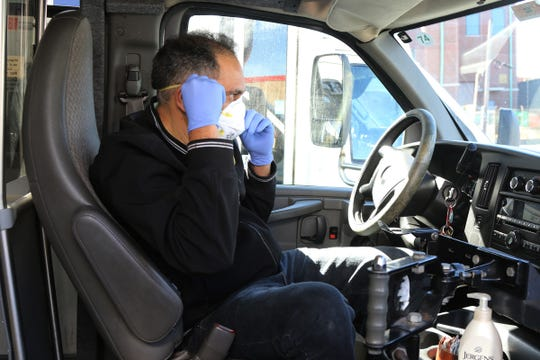 Express Service bus driver Wilson Mynana puts on his mask and wears latex gloves before departing on his 12:30pm run from Paterson to mid-town Manhattan on March 14, 2020. Myana, has driven for the small jitney bus company for 12 years but started wearing the mask and gloves on March 5, to protect himself from the possible transmission of the corona virus as he meets and interacts with many customers through out the day. He slightly opens the window on his door to let in fresh air and waits six hours when he gets home to count the cash he collects from the passengers to give the possible virus a chance to die. He also carries disinfectant soap.