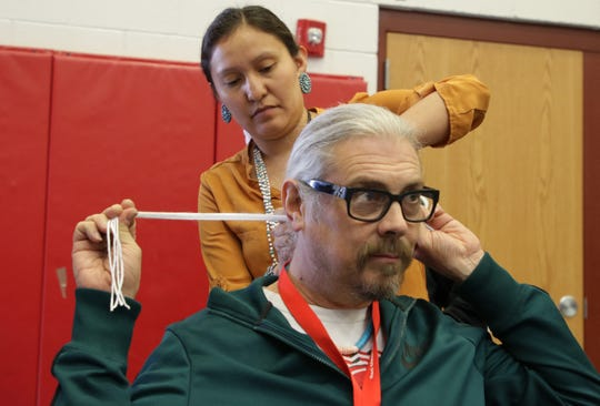 Navajo Technical University student Shalii White ties Red Valley-Cove High School teacher Wesley Cobb's hair into a tsiiyéél during the Diné Maker Nation Faire on March 12 at NTU in Crownpoint.