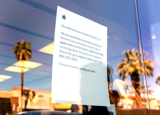Apple Store employees stand outside the closed Palm Desert, Calif., store to answer customers' questions on Saturday, March 14, 2020. Apple announced stores will be closed until March 27th.