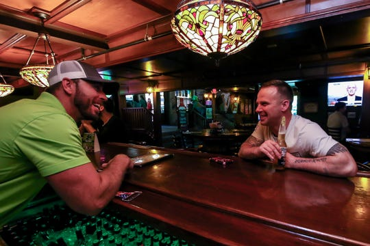 Bartender Charlie Owings, left, chats with Daniel Hicks on Friday, March 13, 2020, at O'Riley's Irish Pub in downtown Pensacola.