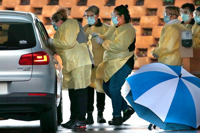 Enfermeras realizan pruebas a presuntos pacientes de COVID-19, sin bajarse del auto.