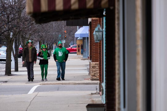 """Mark Roskey, left, walks with Jen Badrak, center, and her husband Phil Stutzky, through downtown Port Huron Saturday, March 14, 2020. The trio said it was their tradition to go out during Pub Crawl, which was originally scheduled for that day but was canceled earlier in the week to help prevent the spread of coronavirus. """"It's tradition,"""" said Stutzky. """"You don't mess with tradition."""""""