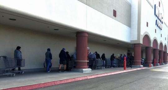 A crowd of people line up outside of WinCo Foods grocery store in Reno.