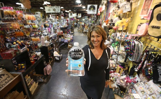 Alayna Alderman, Vice-President and co-owner of the Record Archive, stands at the ready with one of her many bottles of hand sanitizer at the popular music store in Rochester Friday, March 13, 2020.  Every single customer who comes into the store will not be allowed past the front register unless they get hand sanitizer first.