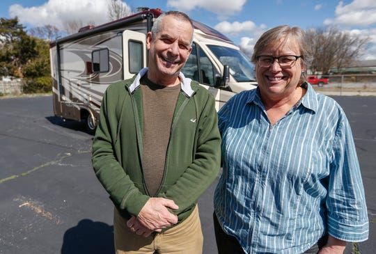 Al Miller, left, and Lynne Myerkord, director of the AIDS Project of the Ozarks, stand in front of the recreational vehicle Miller donated to the organization.