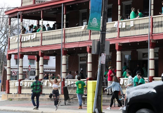 People hang out or pass by the Deer Park Tavern as St. Patrick's Day celebrants take to Newark bars in lesser numbers than might normally be expected of a mild-weather holiday on Main Street Saturday afternoon.