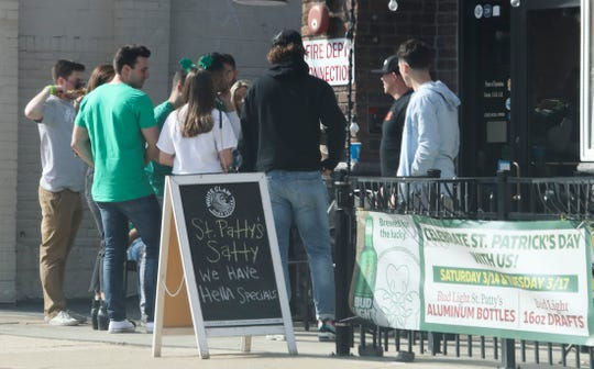 """People line up outside Arena's, which is advertising its """"St. Patty's Satty"""" as St. Patrick's Day celebrants take to Newark bars in lesser numbers than might normally be expected of a mild-weather holiday weekend Saturday afternoon."""