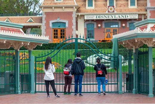 People stand outside the gates of Disneyland Park on the first day of the closure of Disneyland and Disney California Adventure theme parks as fear of the spread of coronavirus continue, in Anaheim, California, on March 14, 2020.