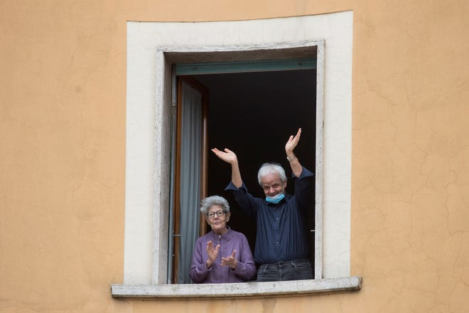 People clap their hands and wave, in Rome, Saturday, March 14, 2020. At noon in Italy, people came out on their balconies, terraces, gardens or simply leaned out from open windows to clap for several minute in a gesture of thanks for the doctors, nurses, other hospital staff and ambulance crews who have been treating and helping infected patients.
